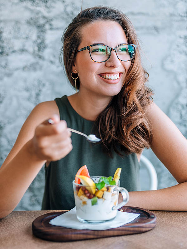 Young cheerful woman eating fruit salad.